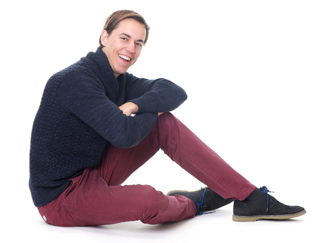Portrait of a relaxed young man sitting and smiling on isolated white background photo