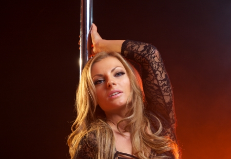 Close up portrait of a sensual female with blond hair with dance pole