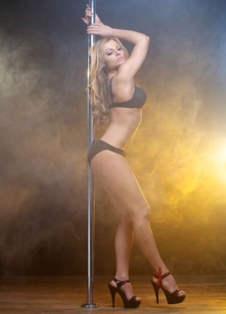 Full body portrait of a sexy slim pole dancer in black lingerie photo