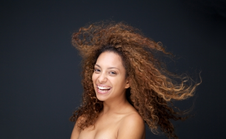 black hair woman: Close up portrait of a beautiful young woman with curly hair laughing