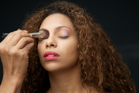Close up portrait of make up application on a beautiful young african american woman with curly hair Stock Photo - 24238511