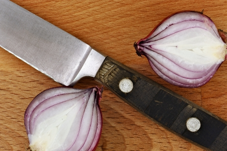 Close up knife with two slices of red onion on cutting board from above photo
