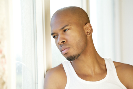 man looking out: Close up portrait of a handsome young man looking out of window