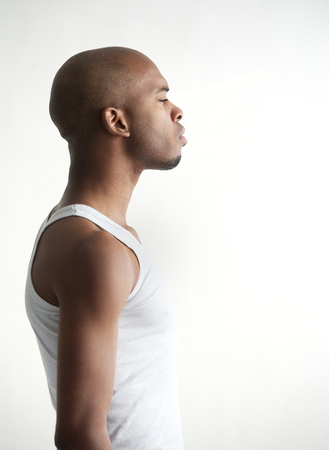 Profile portrait of a black man standing on white background photo