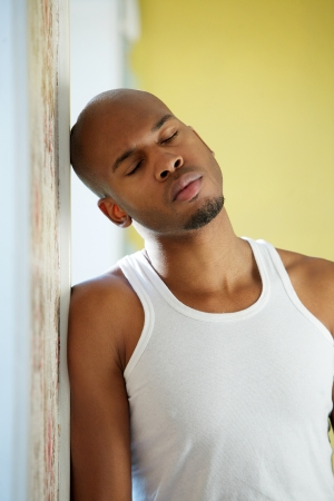Portrait of a man leaning against wall with eyes closed in contemplation photo