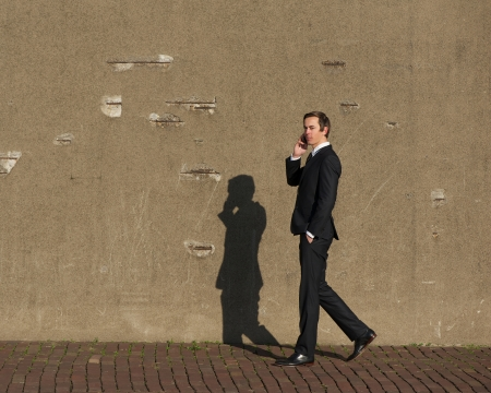 Full body portrait of a young businessman walking and talking on mobile phone photo