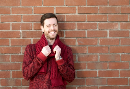 red brick wall: Horizontal portrait of a happy young man smiling outdoors against brick wall background