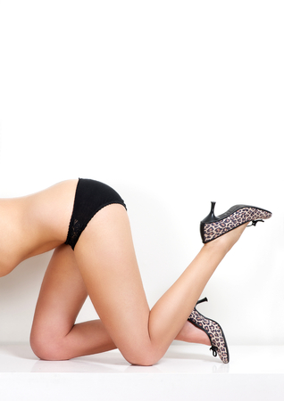 Close up portrait of half female body showing legs and shoes on white background photo
