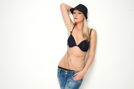 Portrait of a beautiful young blond woman posing in black bra and jeans against white background photo