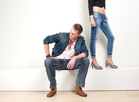 separate: Portrait of a handsome man sitting with a pair of female legs in background Stock Photo
