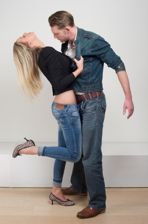 Full body portrait of a young woman holding jacket of attractive male model in passionate pose photo