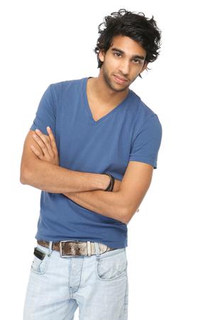 腕を組んで孤立した白い背景に対して立っているカジュアルな若い男の肖像画を閉じる