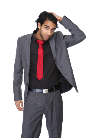 Portrait of a casual business man with hand in hair posing against isolated white background  photo