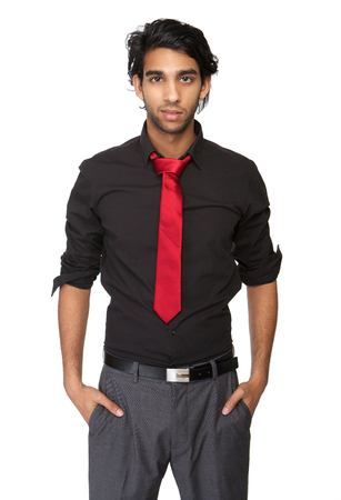 Portrait of a trendy young man in black shirt and tie standing on isolated white background photo
