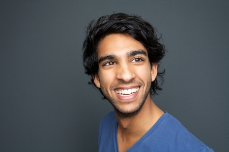 Close up portrait of a happy young man smiling against gray background