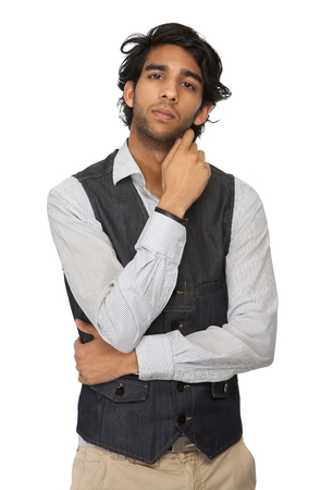 Portrait of a serious young man with hand to face standing on isolated white background photo