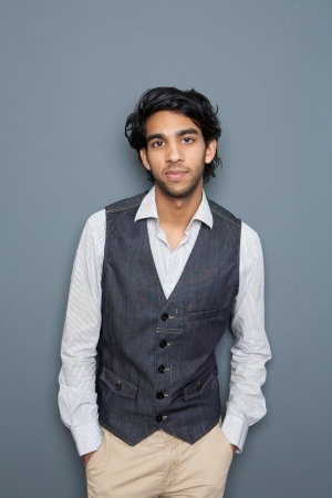 Portrait of a young man standing against gray background with hands in pocket photo