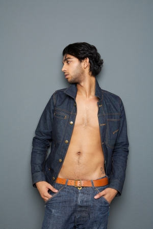 Portrait of a man looking away with open shirt standing against gray background  photo