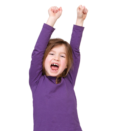 Close up portrait of a young girl cheering with raised arms on isolated white background photo