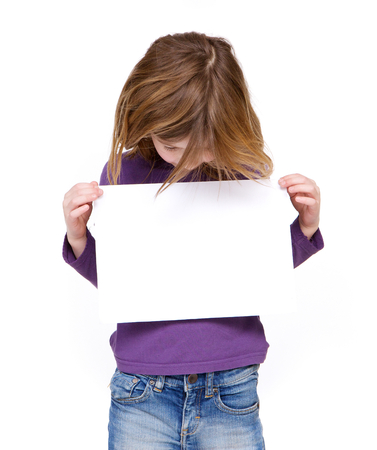 Portrait of a young girl looking at blank sign on isolated white background 版權商用圖片