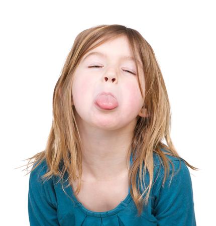 školačka: Portrét mladé dívky s vyplazeným jazykem na bílém pozadí