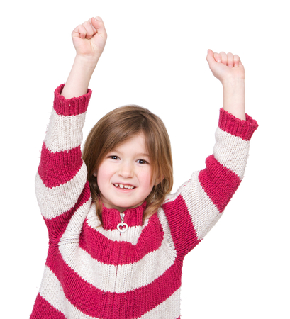 Close up portrait of an adorable young girl with arms raised in success on isolated white background photo
