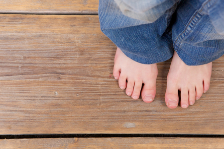teen girls feet: Close up barefoot girl standing on wooden floor - from above