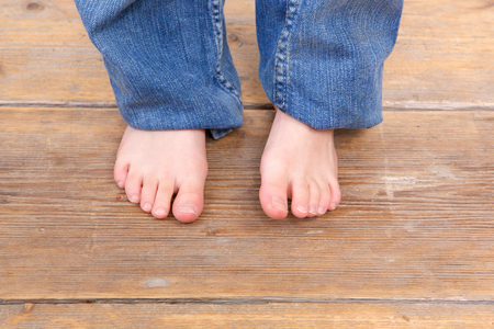 Close up young girl barefoot on wooden floor Stock Photo