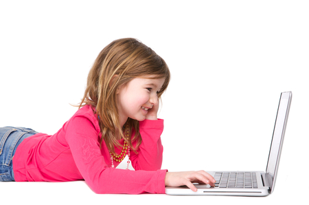 preteens girl: Horizontal portrait of a smiling young girl typing on laptop against isolated white background