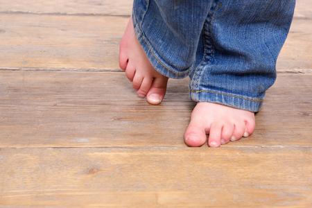 Vooraanzicht lage hoek van een klein meisje met blote voeten op een houten vloer