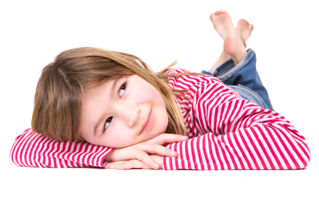 sweet smile: Close up portrait of a young blond girl lying on floor