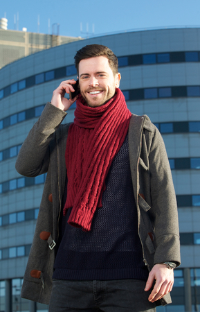 phone conversation: Portrait of a smiling man talking on mobile phone outside building