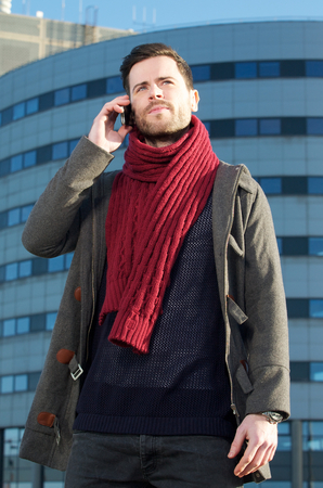 Close up portrait of a trendy man talking on mobile phone outside city building photo
