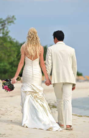Rear view portrait of wedding couple walking on beach  photo