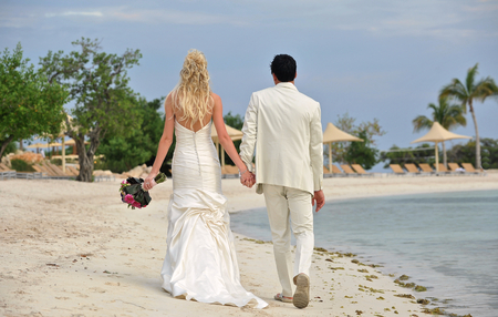 Full length portrait of a bride and groom walking together on beach photo