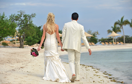 Rear view portrait of husband and wife newlyweds walking on beach together photo