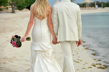 Close up portrait of bride and groom walking hand in hand on beach photo