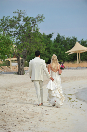 Rear view portrait of a bride and groom walking on beach photo