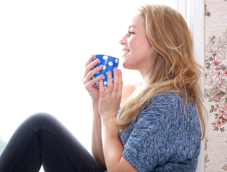 Close up portrait of a young woman relaxing with a cup of coffee at home photo