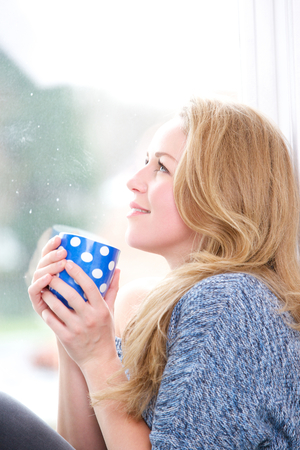 Close up portrait of a beautiful caucasian woman relaxing with a cup of tea by window photo