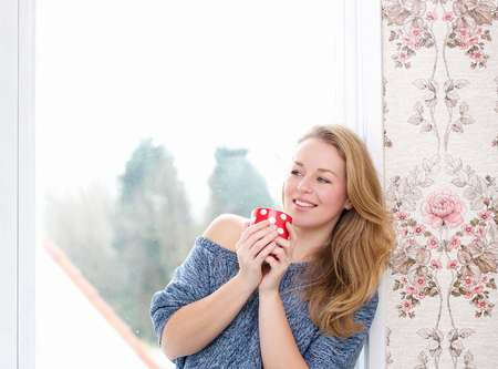 Close up portrait of a young woman relaxing by window with a cup of tea photo