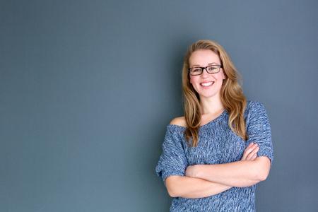 Close up Portrait einer Geschäftsfrau, die gegen grauen Hintergrund mit verschränkten Armen Standard-Bild - 25997730