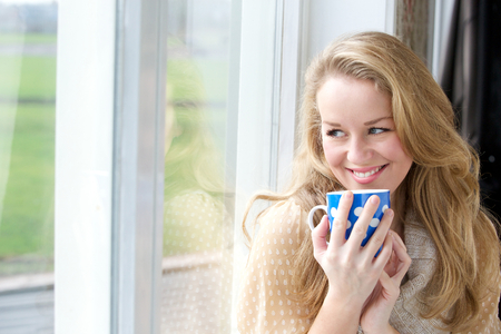 Close up portrait of a smiling young lady holding cup of tea and looking outside through window photo