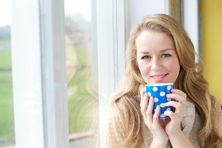 Close up portrait of a smiling young woman drinking cup of tea at home photo