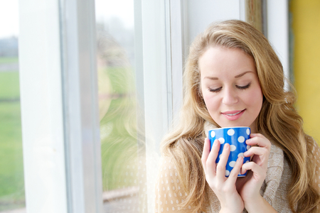 Close up portrait of a beautiful young woman drinking a cup of tea by a window at home photo