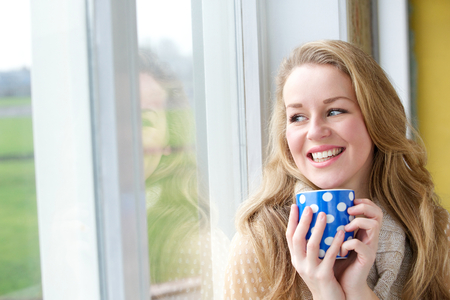 Close up portrait of a young woman smiling with cup of tea and looking outside through window photo