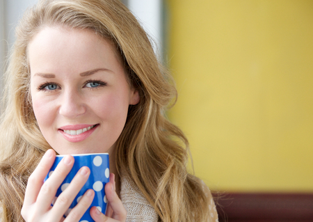 Close up portrait of a beautiful young lady holding tea cup at home photo