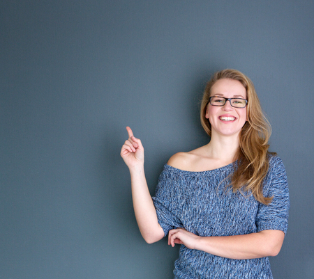 woman pointing up: Close up portrait of a young woman laughing and pointing finger up on gray background