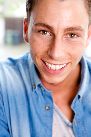 Close up portrait of a happy young man smiling photo