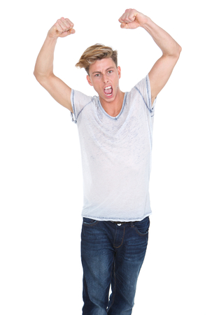 Portrait of a young man celebrating with arms raised on isolated white background photo